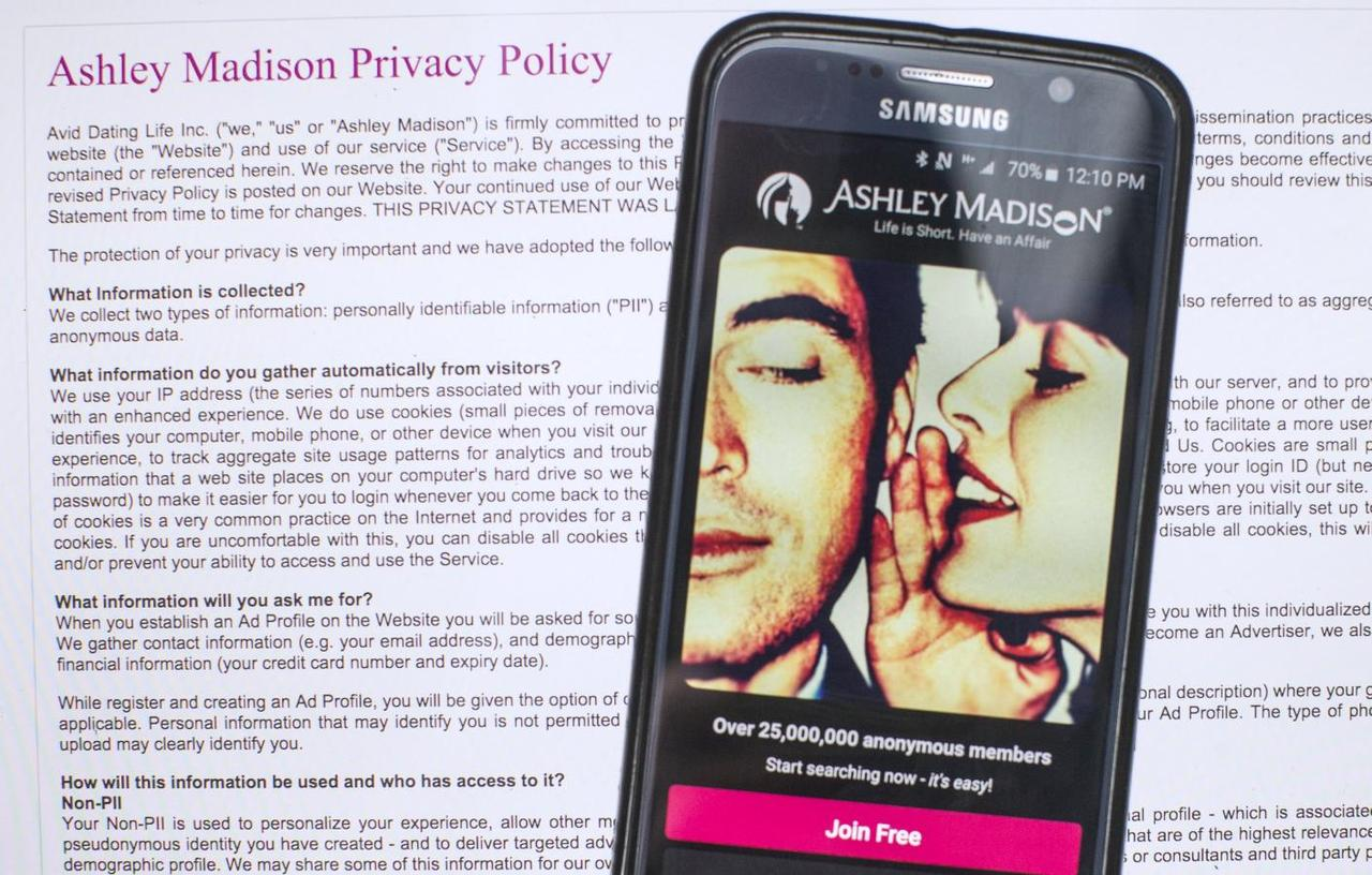 A photo illustration shows the privacy policy of the Ashley Madison website  seen behind a smartphone running the Ashley Madison app in Toronto, August  20, ...