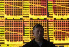 Инвестор у электронного табло в брокерском доме в Ухане 4 марта 2013 года. Китайский фондовый рынок пережил в понедельник самую мрачную торговую сессию со времен мирового финансового кризиса в 2009 году, и основные индексы пробили ключевые уровни поддержки на волне панических распродаж после того, как инвесторы не дождались от Пекина мер помощи для финансовой системы. REUTERS/Stringer