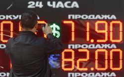 Мужчина фотографирует электронное табло с курсами обмена валют в Москве. 24 августа 2015 года. Рубль дорожает утром вторника вслед за нефтяными котировками, растущими с 6,5-летних минимумов на фоне признаков улучшения ситуации на мировых рынках после обвала накануне, поддержку может оказывать и фактор пика уплаты налогов - сегодня завершаются расчеты по НДПИ, НДС и акцизам. REUTERS/Sergei Karpukhin