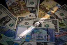 Банкноты тенге и доллара США. Алма-Ата, 21 августа 2015 года. Курс казахского тенге упал во вторник после резкого роста накануне на продажах валютной выручки экспортеров, в ожидании дальнейшего падения российского рубля и низких цен на нефть, сообщили участники рынка. REUTERS/Shamil Zhumatov