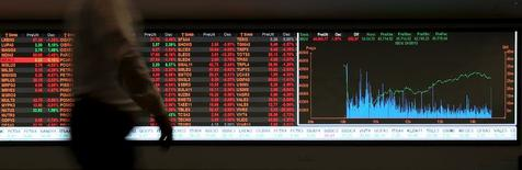 Un hombre pasa frente a un panel con información bursátil en la Bolsa de Valores de Sao Paulo, ago 24 2015. Los temores a una desaceleración más fuerte en China, que provocó un desplome en los mercados mundiales, podrían retrasar una recuperación económica en Brasil que se esperaba para este año, dijo el martes un alto funcionario brasileño.  REUTERS/Paulo Whitaker