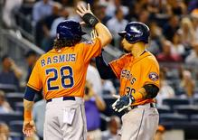 Aug 25, 2015; Bronx, NY, USA; Houston Astros center fielder Carlos Gomez (30) is congratulated by right fielder Colby Rasmus (28) after hitting a three run home run in the seventh inning against the New York Yankees at Yankee Stadium. Andy Marlin-USA TODAY Sports