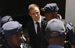 South African Olympic and Paralympic sprinter Oscar Pistorius (C) is escorted to a police van after his sentencing at the North Gauteng High Court in Pretoria October 21, 2014. REUTERS/Siphiwe Sibeko