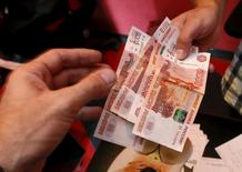 Сотрудник станции техобслуживания автомобилей принимает деньги от клиента в Красноярске 6 августа 2015 года. Рубль взлетел на недельные максимумы на фоне скачка нефтяных цен в русле восходящих тенденций мировых рынков после снижения китайских процентных ставок и уменьшения вероятности повышения ставок ФРС. REUTERS/Ilya Naymushin