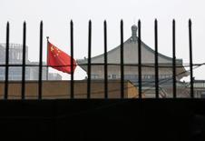 """La bandera de China ondea detrás de una reja en la sede de la Comisión de Reforma y Desarrollo Nacional de China, en Beijing, 12 de julio de 2013. China incrementará los ajustes """"específicos"""" de sus políticas económicas de manera oportuna, reportó el jueves la agencia estatal de noticias Xinhua tras citar al poderoso organismo de planificación del país. REUTERS/Kim Kyung-Hoon"""