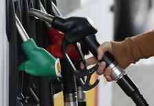 Un cliente se prepara para llenar el estanque de su auto en una gasolinera en Sint Pieters Leeuw, 5 de diciembre de 2014. Los precios del petróleo han caído demasiado y muy rápido, por lo que deberían recuperarse gradualmente el próximo año por una desaceleración del crecimiento de la oferta y la recuperación de la demanda, mostró el martes un sondeo de Reuters. REUTERS/Yves Herman
