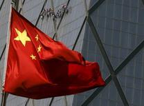 Una bandera de China en un distrito comercial en Beijing, 20 de abril de 2015. El Gabinete chino relajará los requerimientos para las inversiones en activos fijos, con medidas que incluyen la reducción de las exigencias de capital mínimo, indicó el martes un comunicado publicado en Internet. REUTERS/Kim Kyung-Hoon