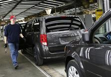 A Fiat Chrysler assembly worker walks past a Dodge Grand Caravan minivan on the final production line at the Windsor Assembly Plant in Windsor, Ontario, February 9, 2015. REUTERS/Rebecca Cook