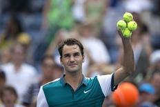 Roger Federer of Switzerland holds a handful of tennis balls before hitting them towards fans after defeating Leonardo Mayer of Argentina in their first round match at the U.S. Open Championships tennis tournament in New York, September 1, 2015.    REUTERS/Carlo Allegri