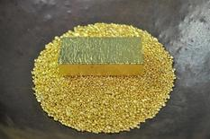 Золотой слиток и гранулы в офисе компании Zlatarna Celje в Целе. 17 апреля 2013 года. Цены на золото снижаются после четырехдневного роста за счет неуверенности в сроке повышения процентных ставок ФРС. REUTERS/Srdjan Zivulovic