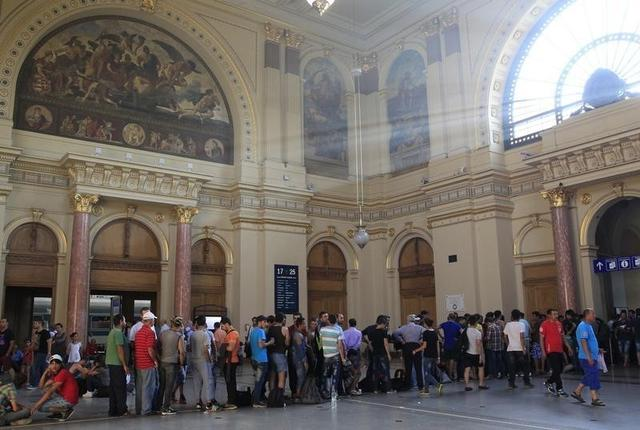People stand in a queue to buy train tickets a the railway station in Budapest, Hungary, August 31, 2015. REUTERS/Bernadett Szabo