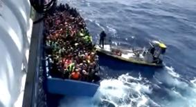 A boat full of migrants is seen next to Swedish ship Poseidon during a rescue operation in the sea off the coast of Libya in this still image taken from an August 26, 2015 video.  REUTERS/Swedish Coast Guard Handout via Reuters TV