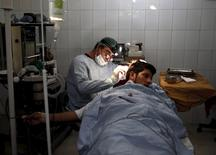 Plastic surgeon Abdul Ghafar Ghayur performs surgery on a patient at Aria City Hospital, in Kabul, Afghanistan August 6, 2015. REUTERS/Ahmad Masood
