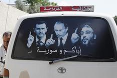 """Постер с изображениями президента Сирии Башара Асада, президента РФ Владимира Путина и лидера """"Хезболлы"""" Хасана Насраллы на стекле микроавтобуса в сирийском городе аль-Кардахах. 26 мая 2014 года. Россия в последние дни отправила в Сирию два танкодесантных корабля, самолеты, а также разместила небольшой контингент морской пехоты, сообщили американские чиновники, тогда как источники в Ливане сообщили, что россияне участвуют в боях на стороне сирийских правительственных сил. REUTERS/Khaled al-Hariri"""