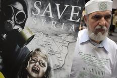 Участник демонстрации по случаю годовщины газовых атак в Сирии. Нью-Йорк, 22 августа 2014 года. Совет безопасности ООН разрешил начать международное расследование, чтобы определить, кто виноват в использовании химического оружия в Сирии. REUTERS/Carlo Allegri