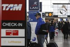 Personas en el Aeropuerto Internacional de Santiago, en Chile, 22 de junio de 2012. Una paralización de trabajadores aeronáuticos en Chile obligó el martes a las aerolíneas a suspender y reprogramar vuelos, mientras miles de pasajeros quedaron varados por el incidente, informaron los manifestantes y aerolíneas. REUTERS/Carlos Vera