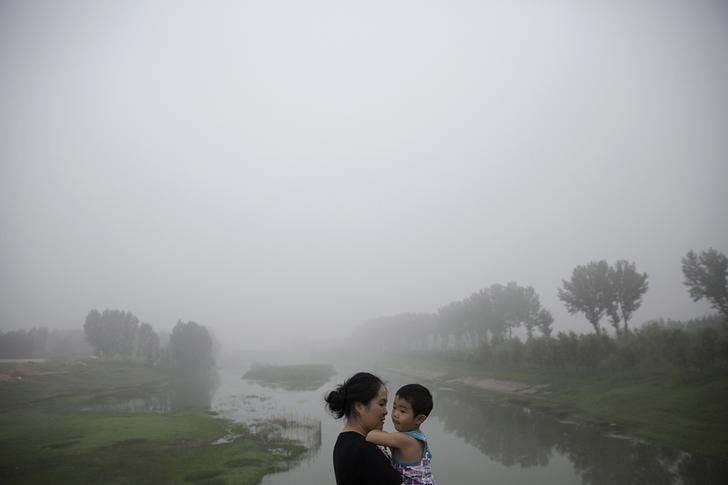 A woman holds a child as travellers wait for the highway from Beijing to China's Hebei Province to reopen after in was closed due to low visibility, on a heavy polluted morning August 3, 2015.  REUTERS/Damir Sagolj
