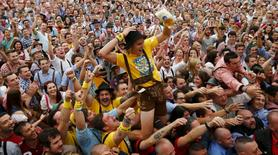 A visitor celebrates as he drinks one of the first mugs of beer after the tapping of the first barrel during the opening ceremony for the 180th Oktoberfest at the Hofbraeu tent in Munich in this September 21, 2013 file photo. REUTERS/Michael Dalder/Files