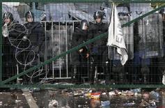 """Венгерские полицейские за забором на границе с Сербией в районе погранпункта Рожке 16 сентября 2015 года. Словения в среду объявила о """"временном"""" восстановлении контроля на границе с Венгрией, став еще одним отступившим от принципа свободы передвижения членом Евросоюза, захлестнутого волной масс, бегущих от войн и бедности на Ближнем Востоке и в Африке. REUTERS/Marko Djurica"""