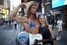 Robert Burck known as the original 'Naked Cowboy' poses for a photo with a woman while wearing his bikini top, which he is wearing due to the recent concerns of topless street performers in Times Square, in the Manhattan borough of New York, August 21, 2015.  REUTERS/Carlo Allegri