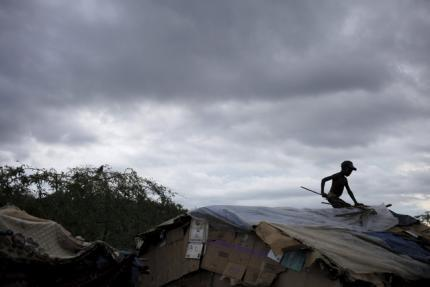Wibens Pierre fixes the roof of a makeshift tent at a refugee camp for Haitians returning from the Dominican Republic on the outskirts of Anse-a-Pitres, Haiti, September 6, 2015. REUTERS/Andres Martinez Casares