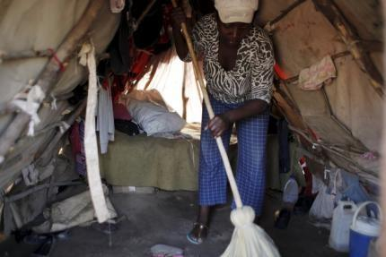 Gasly Laduceur sweeps the dirt floor with a broom inside a makeshift tent at a refugee camp for Haitians returning from the Dominican Republic on the outskirts of Anse-a-Pitres, Haiti, September 7, 2015. REUTERS/Andres Martinez Casares