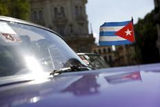 A Cuban flag flies attached on a vintage car in Havana September 18, 2015. REUTERS/Carlos Garcia Rawlins
