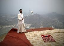 A Muslim pilgrim uses a selfie stick to take pictures atop Mount Thor in the holy city of Mecca ahead of the annual haj pilgrimage September 19, 2015. Mount Thor marks the start of the journey of the Prophet Mohammad and his companion Abu Bakr Al-Sadeeq from Mecca to Medina. It houses Thor cave where Prophet Mohammed is believed to have hid from the people of Quraish before his Hijra (migration) to Medina. REUTERS/Ahmad Masood