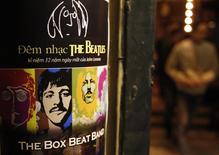 A fan walks near a poster promoting a tribute concert which marks the 32nd death anniversary of British legendary rocker John Lennon of the Beatles at a vintage cafe in Hanoi December 7, 2012. REUTERS/Kham