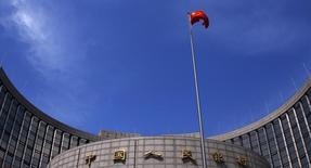 Una bandera de China ondea frente a la sede del Banco Central del país, en Pekín, 16 de mayo de 2014.  El banco central de China dijo el viernes que observará de cerca el comportamiento de los flujos de capital y usará variadas herramientas monetarias para asegurar una adecuada liquidez y un crecimiento razonable en créditos y financiamiento social. REUTERS/Petar Kujundzic