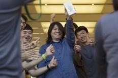 El personal de una tienda apple aplaude mientras uno de sus primero clientes celebra la compra de un móvil iPhone, en una Pekín, 25 de septiembre de 2015. Los nuevos iPhone 6s y 6s Plus llegaban a los comercios el viernes, mientras decenas de personas -y un robot- hacían fila en Sídney en el inicio de un ciclo de ventas a nivel global que será evaluado en busca de señales para saber cuánto jugo le queda al dispositivo insignia de Apple Inc. REUTERS/Damir Sagolj