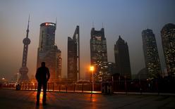 Un hombre mirando el distrito financiero de Pudong, en Shanghái, 20 de noviembre de 2013. El crecimiento económico de China se mantendrá estable en el tercer trimestre porque el impacto del hundimiento del mercado de acciones será limitado, señaló el viernes la Oficina Nacional de Estadísticas. REUTERS/Carlos Barria/Files