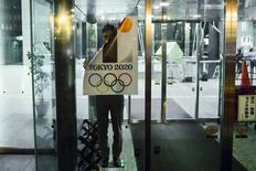 An employee takes down a placard with the Tokyo 2020 Olympic Games emblem during staged event for the media at the Tokyo Metropolitan Government Building in Tokyo September 1, 2015. REUTERS/Thomas Peter