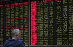 Un inversor frente a un tablero electrónico que muestra la información de las acciones, en una correduría en Pekín, China, 25 de septiembre de 2015. Las acciones chinas subieron el lunes en un débil volumen de negocios, luego de que los inversores hicieron caso omiso a datos que revelaron que las ganancias de las empresas industriales chinas cayeron en agosto a su ritmo más acelerado en cuatro años. REUTERS/China Daily