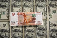 Долларовые и рублевая купюры в Сараево 9 марта 2015 года. Рубль ушел в плюс на дневных торгах вторника за счет текущего роста нефтяных котировок и надежд на сотрудничество России и США в сирийском конфликте после периода охлаждения в отношениях двух стран. REUTERS/Dado Ruvic