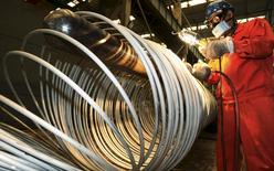 A worker polishes steel coils at a factory in Dalian, Liaoning province, China, in this September 1, 2015 file picture.  REUTERS/China Daily/Files