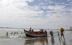 Un pescador acarrea una caja con pescado luego de llegar en un bote de pesca en el puerto de Pimentel, en la costa de Lambayeque, Perú, 17 de octubre de 2014. La producción del vital sector de minería e hidrocarburos en Perú creció un 6,10 por ciento interanual en agosto, mostraron el jueves indicadores adelantados del Gobierno, impulsada por el repunte de la extracción de metales como el cobre y la plata. REUTERS/ Mariana Bazo