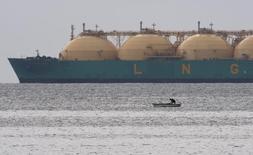 Рыбак на фоне СПГ-танкера близ Гаваны 28 июня 2009 года. Производство сжиженного природного газа (СПГ) на единственном российском СПГ-заводе на Сахалине сохранится в 2016 году на уровне 10,8 миллиона тонн, несмотря на вялый спрос на азиатском рынке, сообщил Рейтер глава оператора проекта компании Sakhalin Energy Роман Дашков в письменном интервью, полученном по электронной почте. REUTERS/Desmond Boylan