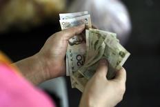 Una persona cuenta yuanes en un mercado en Pekín, ago 12 2015. Las autoridades de China deberían seguir aplicando reformas estructurales para poner a la segunda mayor economía del mundo en una senda del crecimiento sostenible, aunque es probable que la expansión del PIB del país se desacelere a un 6,3 por ciento en 2016, dijo el martes el Fondo Monetario Internacional.  REUTERS/Jason Lee