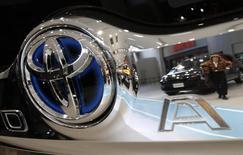 Una persona se refleja en el logo de un auto Toyota, en la sala de exhibición de la compañía en Tokio, 4 de febrero de  2015. Toyota Motor Corp dijo que buscaría introducir en el mercado para el año 2020, aproximadamente, autos que puedan de forma autónoma cambiar de carril, moverse entre el tráfico y adelantar a otros vehículos en autopistas, en su intento por ponerse al día en el nuevo sector de los coches sin conductor. REUTERS/Yuya Shino
