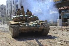 Танк сирийских правительственных сил в пригороде Дамаска. 14 августа 2014 года. Армия сирийского президента Башара Асада и местное ополчение в среду пошли в сухопутную атаку на позиции повстанцев в Сирии при российской поддержке с воздуха, что выглядело как их первое масштабное скоординированное наступление с момента вмешательства Москвы на прошлой неделе, сообщил наблюдатель. REUTERS/SANA/Handout via Reuters