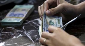 Un empleado contando dólares en una casa de cambios en Hanoi, ago 12, 2015. El optimismo sobre el crecimiento económico global fomentó el apetito por el riesgo e hizo subir al dólar frente al euro y el franco suizo, mientras que el yen se apreció ante la moneda estadounidense después de que el Banco de Japón mantuvo sin cambios su política monetaria.  REUTERS/Kham