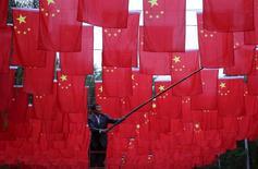 Homem pendurando bandeiras chinesas em Pequim.  29/09/2015   REUTERS/China Daily