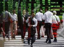 Peatones se reflejan en un tablero electrónico que muestra la información de las acciones, en Tokio, Japón, 29 de septiembre de 2015. Las bolsas de Asia repuntaban el viernes, siguiendo la dirección de un salto en los precios del petróleo y las ganancias de Wall Street, después de que las minutas de la última reunión de la Reserva Federal redujeron aún más las expectativas de un alza inminente en las tasas de interés de Estados Unidos. REUTERS/Issei Kato