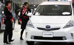 Showroom staff chat next to a Toyota Motor Corp Prius Alpha at its showroom in Tokyo February 4, 2014. REUTERS/Yuya Shino