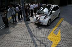 Members of the media watch as an autonomous self-driving vehicle goes onto the road during a demonstration at one-north business park in Singapore October 12, 2015.    REUTERS/Edgar Su