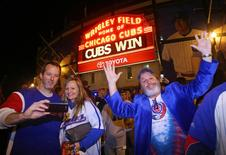 Chicago Cubs fans including Joe Downs (R) celebrate outside of Wrigley Field after game four of the NLDS against the St. Louis Cardinals in Chicago, Illinois, in this October 13, 2015 file photo.   Jerry Lai-USA TODAY Sports/Files