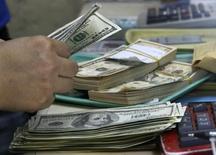 Работник обменного пункта в Маниле считает доллары. 19 сентября 2013 года. Центробанк Казахстана будет продавать на валютном рынке доллары из государственного нефтяного фонда, а не свои собственные резервы, и планирует продать не менее $3 миллиардов до конца октября, сообщил банк в четверг. REUTERS/Romeo Ranoco