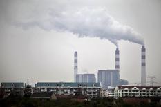 Дым поднимается над трубами завода в Шанхае 28 ноября 2009 года. Темпы экономического роста Китая опустились ниже 7 процентов впервые с мирового финансового кризиса, частично пострадав из-за замедления инвестиций.  REUTERS/Nir Elias