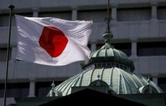 Японский флаг на крыше здания Банка Японии в Токио. 22 мая 2015 года. Банк Японии подтвердил оптимистичные прогнозы относительно экономической ситуации в девяти регионах страны, подчеркнув, что последствия замедления в Китае пока невелики и отсутствует острая необходимость в дальнейшем стимулировании экономики. REUTERS/Toru Hanai